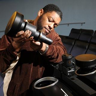 Spitz service technician installs a projector lens